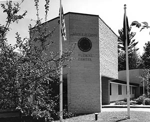 Elliott Alumni Center entrance with flags in the foreground, ca. 1970s.