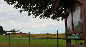 View of barn at Kingman Farm from Knox Marsh Road parking lot with sign in foreground, July 2016.