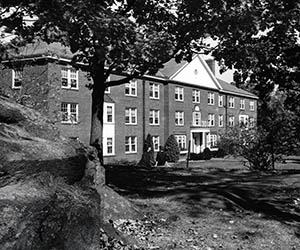 Front of Sawyer Hall with trees and large rock in the foreground.