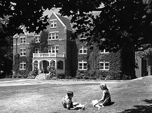 Smith Hall with students two students socializing on lawn, taken by R.Merritt, 1965.