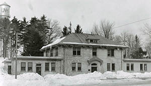 Taylor Hall with snowdrifts in foreground and UNH water tank in background, taken by Clement Moran in February 1935.