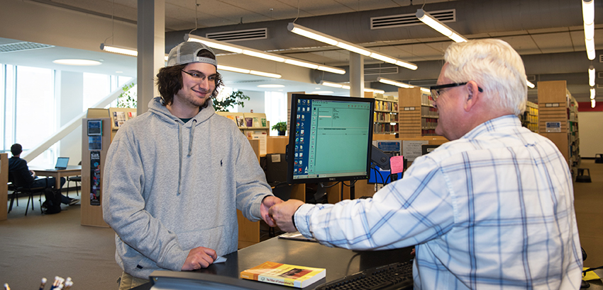 student getting help at the library desk