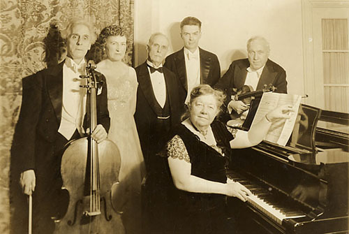 Amy Beach sitting at piano with musicians standing behind her