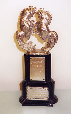Two gold roosters on a trophy