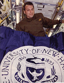 UNH flag and Linnehan in space shuttle