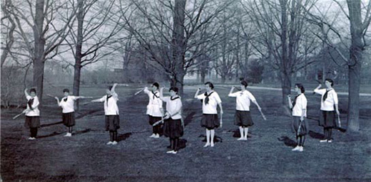 Group of women exercise outside with clubs