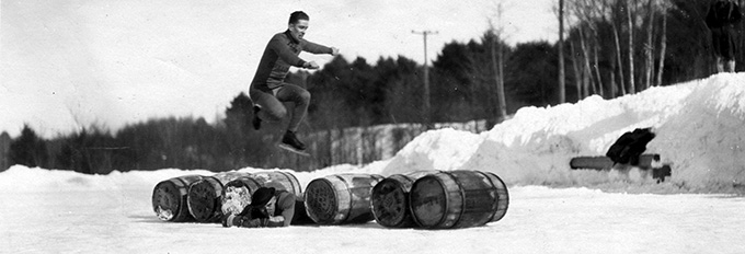 A skating man jumps over six barrels and another man.