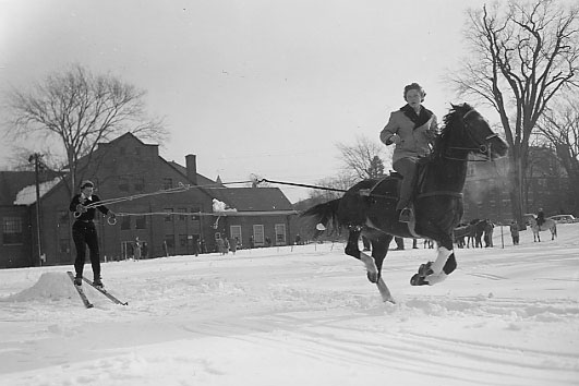 A women riding a horse in the snow pulls another figure on skis