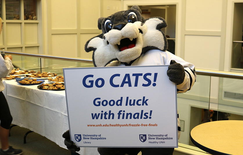 UNH mascot holding good luck sign for students