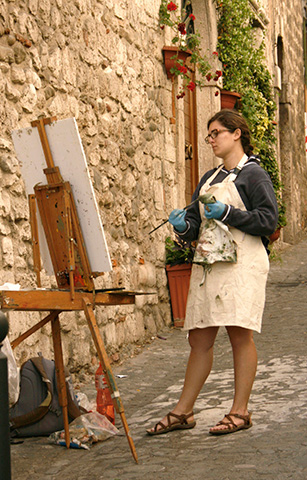 Student considers her canvas painting outside in Italy
